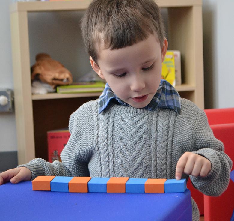Boy counting blocks.
